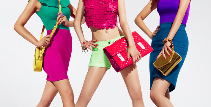 Fashion shopping image with colourful styles. 3 women with purses isolated on white background