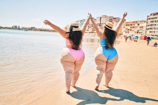 Two plus size overweight sisters twins women happy and proud of their bodies walking at the beach on summer holidays