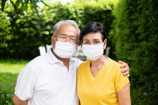 Senior old Asian couple, wearing face mask to protect coronavirus covid-19