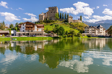 Laudegg Castle is reflected in the lake below on a beautiful sunny day, Ladis, Serfaus, Tyrol, Austria