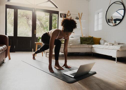 African American teen practising yoga flow watching video on laptop in modern lounge