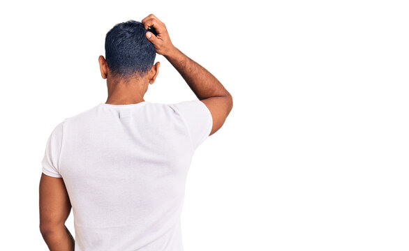 Young latin man wearing casual clothes backwards thinking about doubt with hand on head