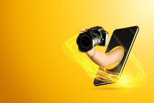 Hand holds a camera through the smartphone screen on a yellow background. Concept of stay at home, coronavirus, way out, camera of a modern smartphone.