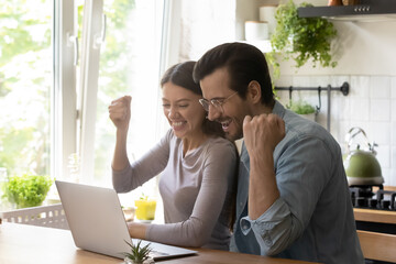 Overjoyed young married couple making yes gesture, celebrating online lottery win or family success...
