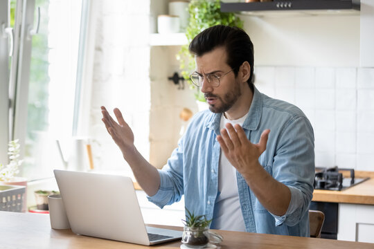 Frustrated angry young man in eyeglasses looking at laptop screen, feeling nervous about bad device work or poor internet connection in kitchen. Unhappy shocked guy reading message with bad news.