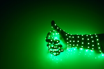 thumbs up hand covered with green led lights, illuminated background