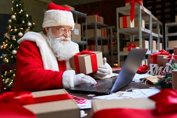 Photo sur Plexiglas Dinosaurs Happy old Santa Claus wearing costume holding gift box using laptop computer sitting at workshop table on Merry Christmas eve. Ecommerce website xmas time holiday online shopping sale concept.
