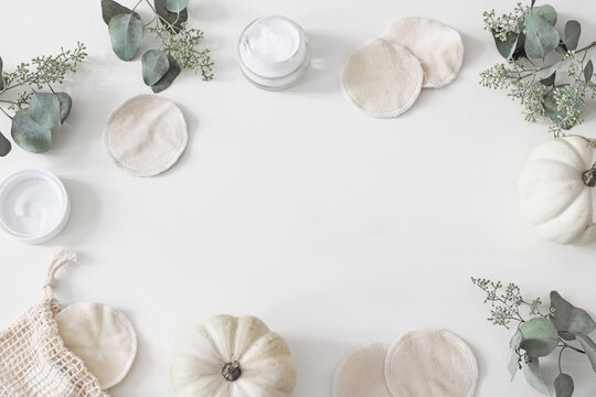 Decorative cosmetics frame. Organic cotton reusable round pads for make up removal. Eucalyptus branches, pumpkins.and moisturizer on white table background. Zero waste concept. Flat lay, top view.