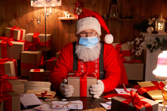 Old funny bearded Santa Claus wearing face mask, holding gift box preparing for xmas eve sitting at cozy home table late in night with presents. Merry Christmas Covid 19 coronavirus safe delivery.
