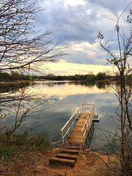 Portrait view of a floating wooden dock at a lake at sunset