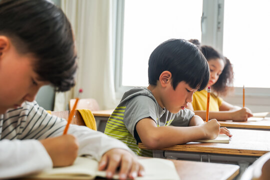 Asian school children sitting at desk in school writing in note book with pencil, studying, education, learning. Male and female students in classroom. Boy and girl in elementary age