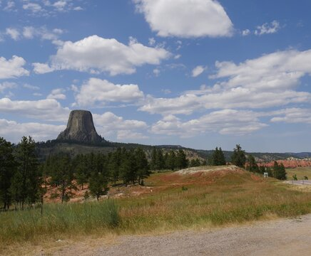 Wide view of the Devils Tower in Wyoming, America's first national monument, with gorgeous clouds in the skies.