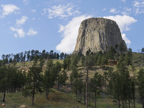 Medium upward shot of the Devils Tower in Wyoming with beautiful clouds in the skies.