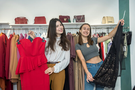 Two women choose modern dress in a store