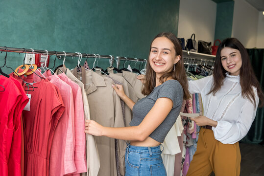 Two friendly girls spending time for shopping in  fashion store