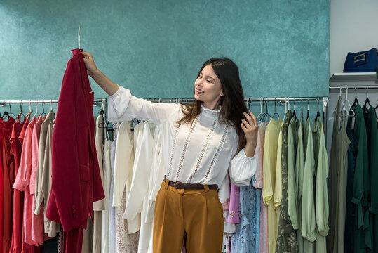Beautiful young woman choosing jacket at clothes shop