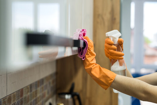 woman in rubber gloves and cleaning the kitchen counter with sponge
