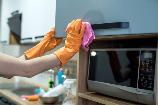 Woman in  rubber gloves cleaning dirty surface in kitchen