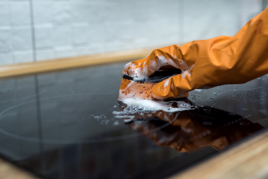 woman washing modern  cooktop cooking panel in kitchen
