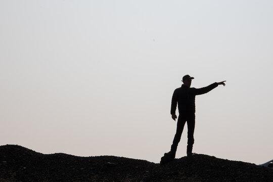 silhouette d'un homme marchant sur la crête d'une montagne