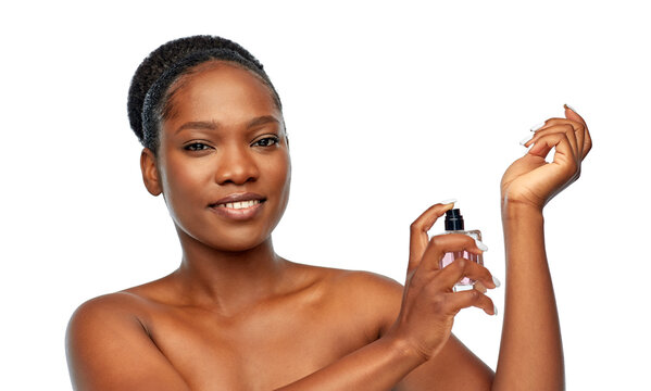 beauty and people concept - portrait of happy smiling young african american woman with bare shoulders with perfume over white background