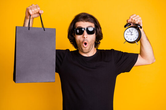 Photo of young man showing alarm clock dial mall packet surprised expression t-shirt sunglass isolated yellow color background