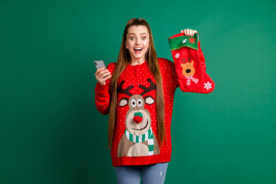 Photo of attractive excited lady hold newyear stocking x-mas eve presents telephone shopping internet buy gifts family tradition wear red ugly pullover isolated green color background