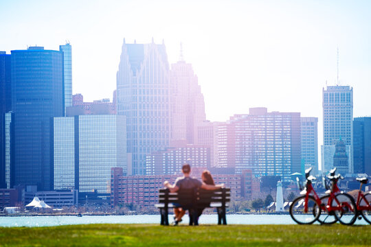 Lovely couple sit in the bench on Sunset Point over Detroit river and view of downtown on sunny day from Belle Isle