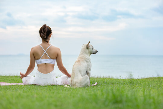 Asian young woman practice yoga lotus pose to meditation with dog on the beach feeling so happiness and cheerful,Travel in tropical beach in Thailand,vacations and relaxation Concept