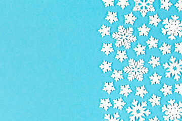 Wall Mural - Top view of winter ornament made of white snowflakes on colorful background. Happy New Year concept with copy space