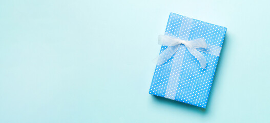Wall Mural - Top view Christmas present box with white bow on blue background with copy space