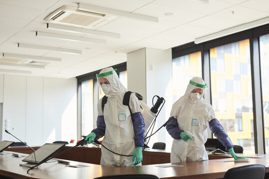 Wide angle portrait of two sanitation workers wearing hazmat suits cleaning and disinfecting conference room in office, copy space