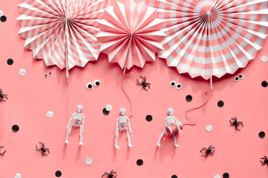 Pink Halloween, flat lay. Stripy paper fans, spiders, skeletons, googly eyes. Black white confetti.