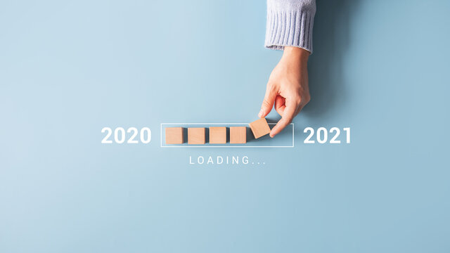 Loading new year 2020 to 2021 with hand putting wood cube in progress bar.