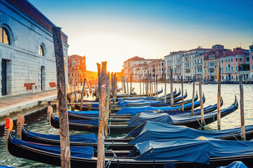 Gondolas moored docked on pier of Grand Canal waterway in Venice. Baroque style buildings along Canal Grande background. View against sun. Amazing Venice cityscape at sunset. Veneto Region, Italy