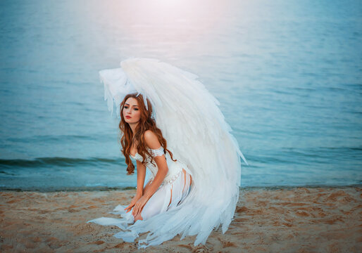 Young beautiful woman fallen sad angel sits on the sea beach. Creative sexy costume, huge artificial bird wings and white vintage dress. Adult girl with sad face of repentance. Artwork photo