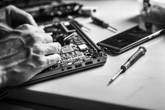 The laptop is located on the desktop. The computer service technician opens the lid with a screwdriver because he wants to install new components in it. Black and white.