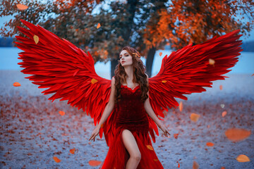 Young beautiful woman fallen angel stands in the park near a tree with orange falling leaves. Creative red suit, huge artificial bird wings and elegant dress. Wind magic whirls the autumn foliage