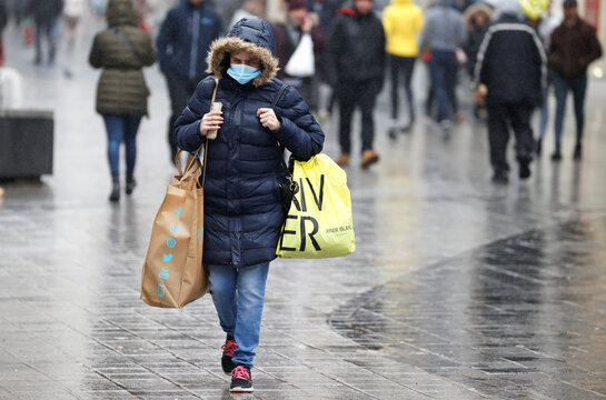 A woman wearing a face mask carries shopping bags in Liverpool