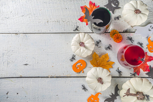 Halloween  cocktails. Witch styled mulled wine drinks, on white wooden background with Halloween decoration, top view copy space