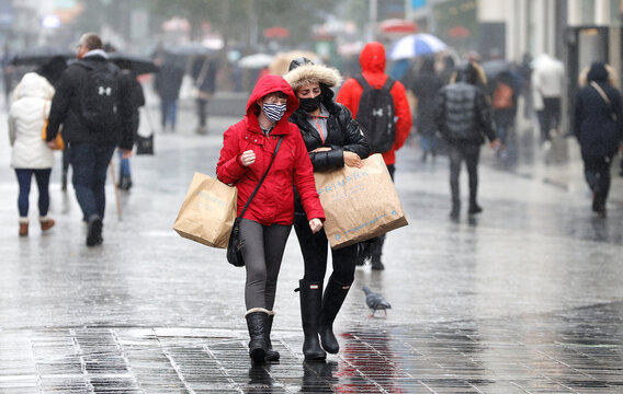Women wearing face masks carry shopping bags in Liverpool