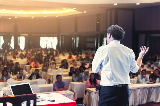 Asian businessman giving speech presentation stage meeting hall conference professional boss chief executive officer company talk lecture seminar coaching educator with people audience in background
