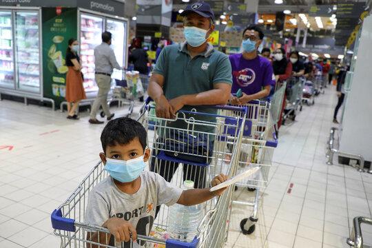 People line up to shop at a supermarket in Subang Jaya