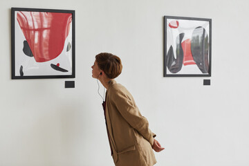 Wide angle portrait of tattooed young woman looking at paintings and listening to audio guide at...