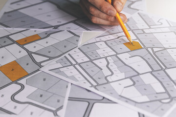 Fototapeta hand with pencil on cadastral map - choose and buy a building plot for house construction