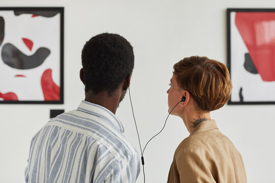 Back view portrait of two young people looking at paintings and sharing audio guide while exploring modern art gallery exhibition, copy space