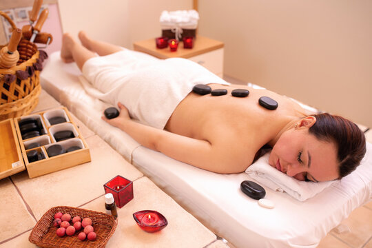 Mature woman in spa having a healing volcanic stone therapy