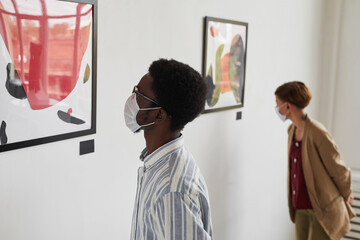Photo sur Plexiglas Dinosaurs Portrait of two young people looking at paintings while wearing masks at modern art gallery exhibition, copy space