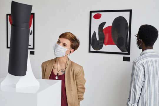 Portrait of two young people looking at paintings and sculptures while wearing masks and exploring modern art gallery exhibition, copy space