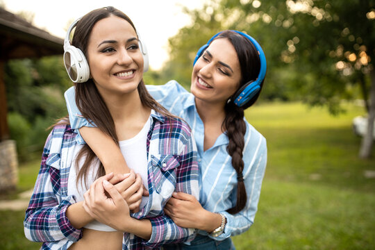 Two girls with headphones in a hug